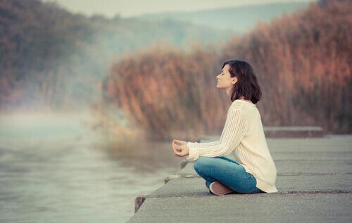 Vrouw beoefent mindfulness aan een meer