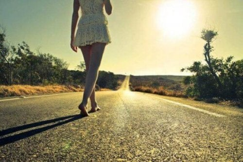 Vrouw loopt blootsvoets op een weg