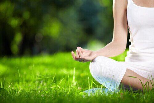 Vrouw mediteert in het gras