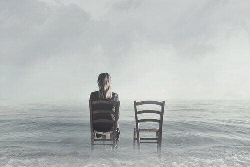 Vrouw op stoel in het water naast een lege stoel
