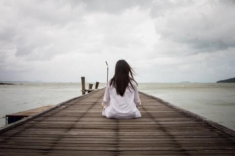 Vrouw zit op een pier