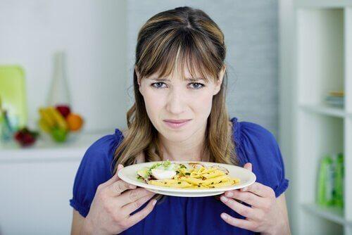 Vrouw walgt van bord eten
