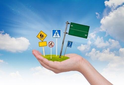 Een hand houdt verkeersborden vast