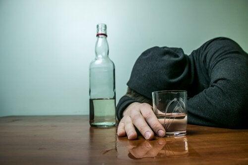 Dronken man ligt met zijn hoofd op tafel