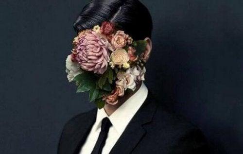 Man met bos bloemen voor zijn gezicht