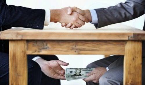 Twee mannen die geld overhandigen onder tafel