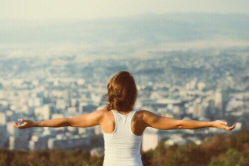Vrouw staat met de armen gespreid en kijkt uit over een stad