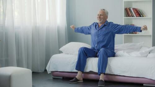 Het belang van een goede nachtrust oudere meneer rekt zich uit