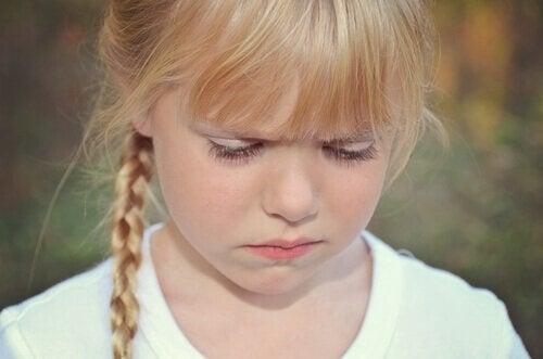 Meisje dat huilend omlaag kijkt