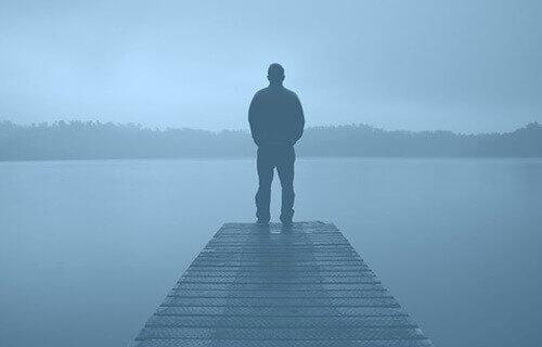 Man staat op pier in de mist