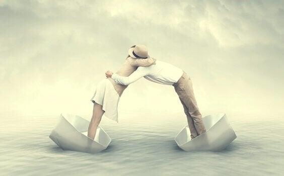 Koppel omhelst elkaar in twee veschillende bootjes