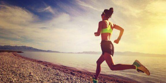 Vrouw die over het strand aan het hardlopen is