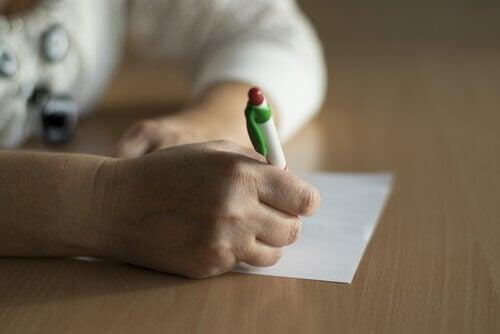 Persoon schrijft op een papier