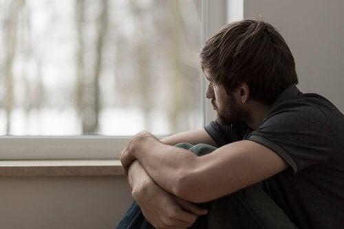 Man met emotioneel leed kijkt uit het raam