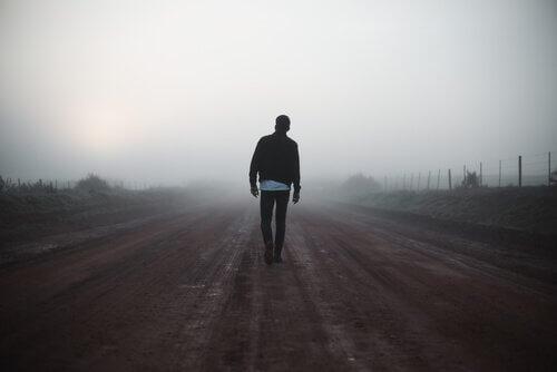 Man loopt over een verlaten weg