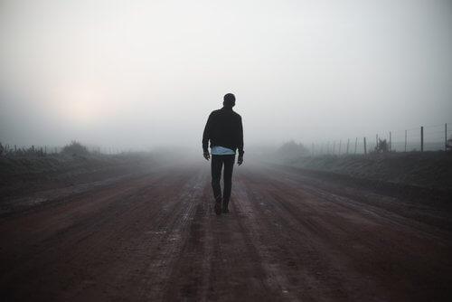 Man die over verlaten weg loopt