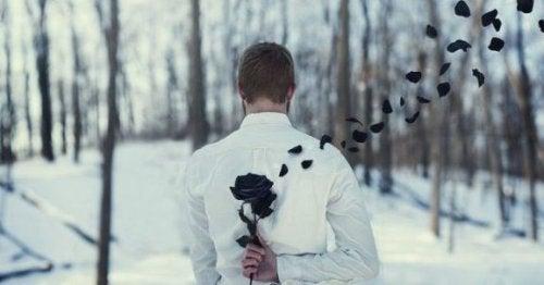 Man houdt zwarte roos achter rug