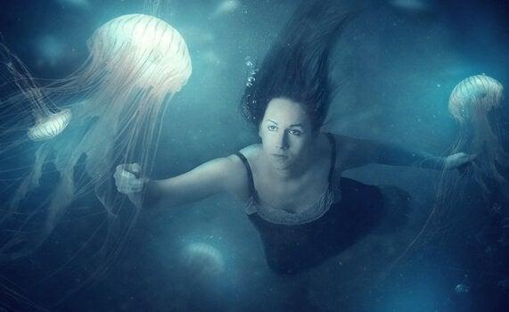 Vrouw zwemmend tussen kwallen