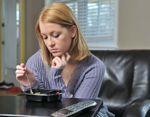 Eenzame vrouw zit aan tafel te eten