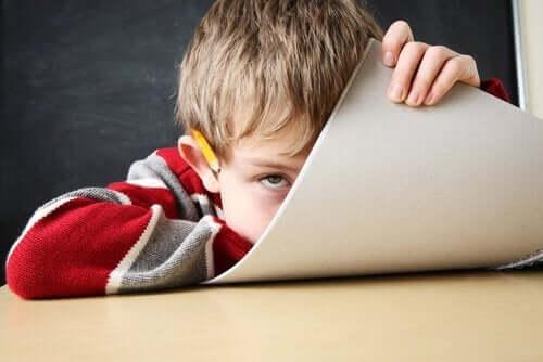 Een jongetje verschuilt zich achter papier