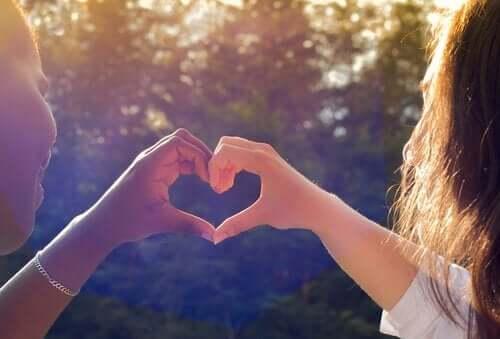 Twee vriendinnen vormen een hart met hun handen