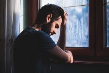 Man staat droevig bij het raam