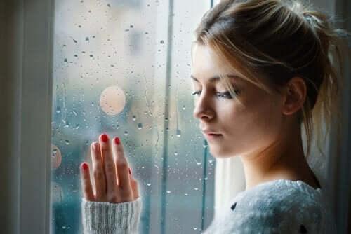 Droevige vrouw die bij een raam staat