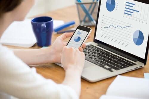 Vrouw bekijkt grafiek op haar mobiele telefoon en computer