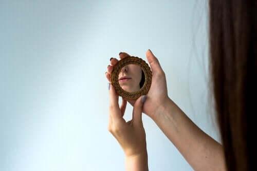 Een vrouw kijkt in een kleine spiegel