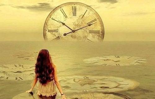 Vrouw kijkt naar klok die ondergaat in zee
