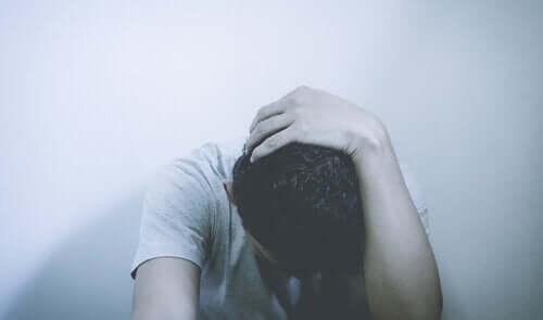 Een man zit in elkaar gedoken tegen een muur