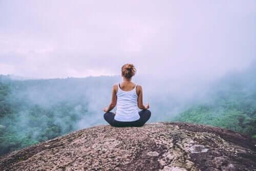 Vrouw mediteert op de top van een berg