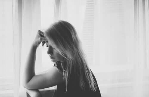 Zwart-wit foto van een vrouw voor een raam