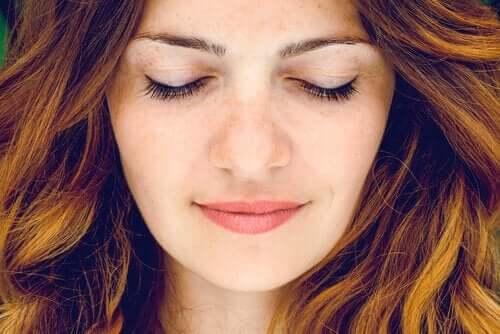 Een vrouw glimlacht met de ogen dicht