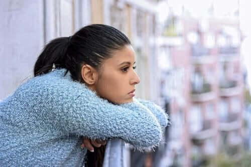 Vrouw leunt op de rand van het balkon