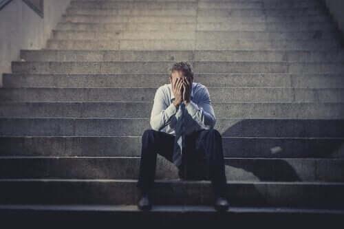 Ontslagen man zit op de trap van een gebouw