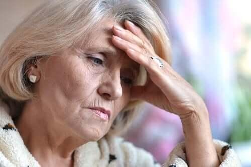 Een oudere vrouw houdt vermoeid haar hand tegen haar hoofd