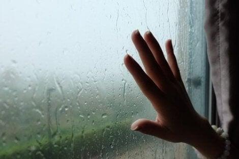 Een hand tegen een beslagen raam