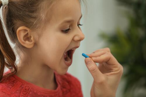 Een kind slikt een pil