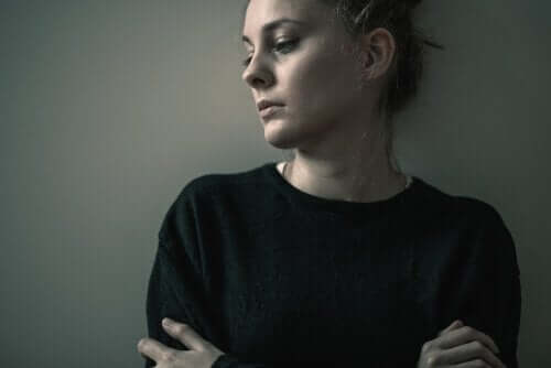 Een vrouw leunt tegen de muur en denkt na