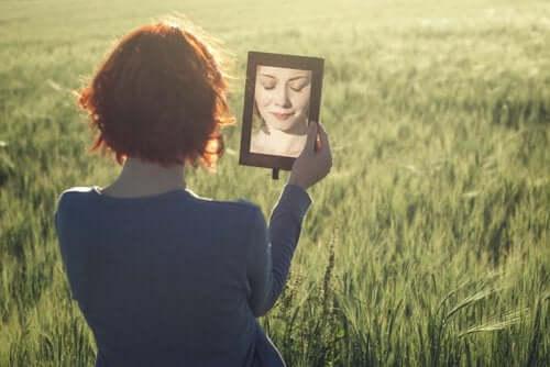 Een vrouw in een veld kijkt in een spiegel