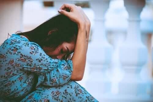 Een verdrietige vrouw zit met het hoofd in de handen