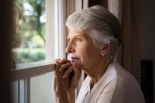 Oudere vrouw kijkt uit het raam
