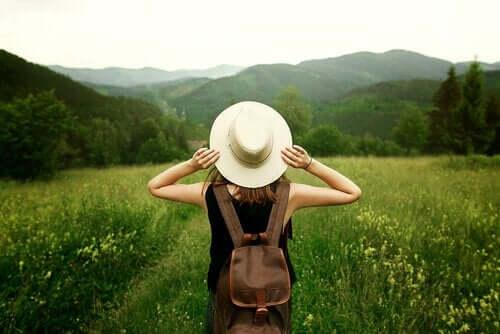 Een vrouw staat in een vallei en kijkt naar de bergen