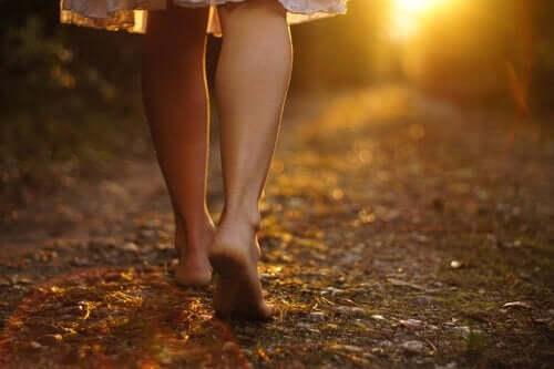 Een vrouw loopt op blote voeten over een zandweg