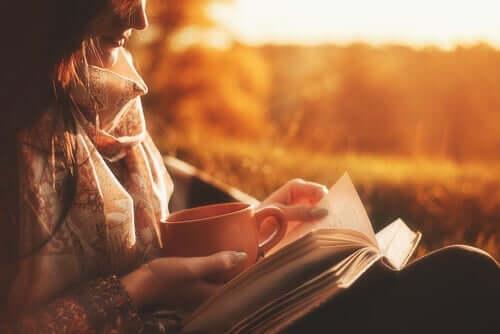 Een vrouw leest met een kop koffie