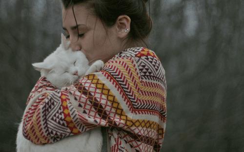Een vrouw knuffelt een kat
