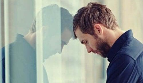 Man leunt met zijn hoofd tegen het raam