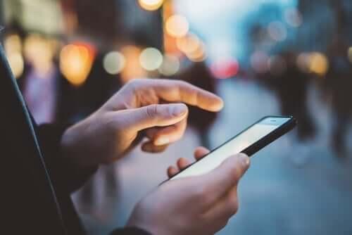 Een man typt op zijn mobiele telefoon