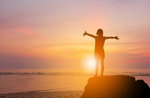 Een vrouw staat met gespreide armen op een rots